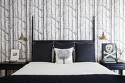 Pattered wallpaper behind black and white bedding.