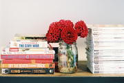 A shelf of books, magazines, and a vase of flowers