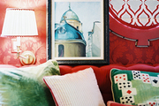 Framed art in a sitting room with red wallpaper and a red sectional