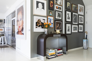 A gallery wall of art and photography surround a New York City apartment's entryway