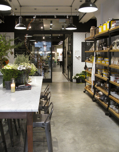 Retail Store Design - Open shelves of gourmet goods in a room with a marble-topped table and industrial bar stools