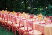 An outdoor dining table set with pink chairs and orange accents