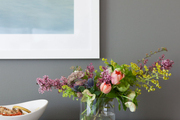 Colorful flowers in glass vase in front of white framed art.