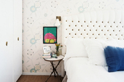 A white tufted headboard paired with floral-patterned wallpaper
