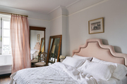 Padded pink headboard with white bedding and matching pink drapes.