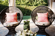 A pair of black wicker chairs with floral cushions on a patio