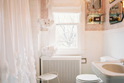 A ruffled shower curtain and pink wallpaper in a bathroom