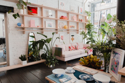 A retail store with a pink sofa and wooden shelving.