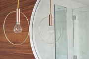 Circles echoing in a mirror and hanging lamp fixture in a Manhattan bathroom