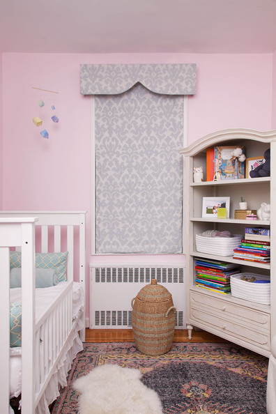 Sheepskin Rug - A pelmet box window treatment, wooden bookcase, and hand-knotted area rug in a nursery