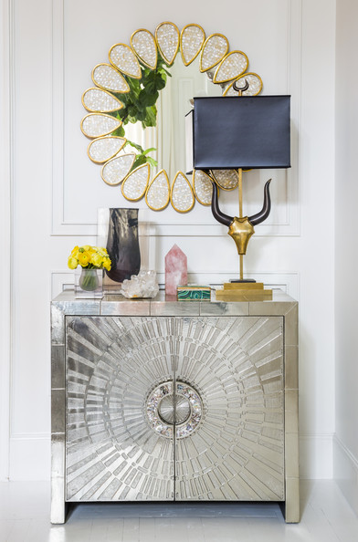 Silver - A console topped with a table lamp, vases, and decorative objets; wall art above
