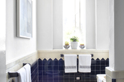 A bathroom with tiled walls, an ikat bath mat, and a Moroccan stool