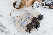 Fashion and accessory pieces on top of a marble table.