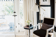 Layered rugs and a brass floor lamp in a bedroom with french doors and deep-brown walls