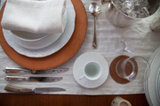 A tabletop display of white dinnerware and a leather charger