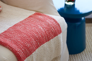 Striped throw on sofa next to small table with flowers.