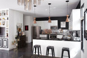 A trio of pendant lamps hang over a black & white kitchen