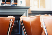 A grouping of leather chairs by a gray fireplace mantel
