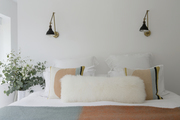 A modern farmhouse style bedroom with a furry white pillow and black wall sconces.