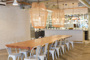 Long natural wood table with large white chairs and large pendent lights.