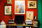 A TV surrounded by artwork and stacks of books
