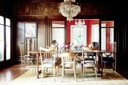 A regal dining room with a chandelier and wooden walls.