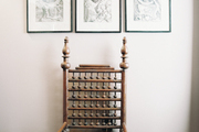A grouping of framed art above a wooden chair