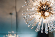 A glass chandelier in a dining room with mirrored walls