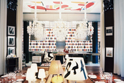 A restaurant boasting leather banquettes and a colorful ceiling