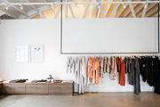 A minimalist retails store with black clothing rack.
