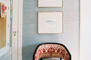 Blue grass-cloth wallpaper and a patterned chair in a bedroom