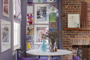 A gallery wall of art beside a brick fireplace in a dining space