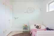 A whimsical kid's room with a soft green wall.