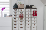 Various shoes and handbags sitting on top of bedroom storage units.