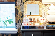 A tray of bar essentials and a rope-frame mirror on a gray cabinet