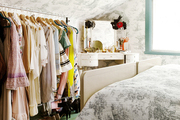 Toile wallpaper and a rolling rack of clothes in a bedroom