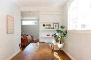 A minimalist dining room with farmhouse chairs and table.