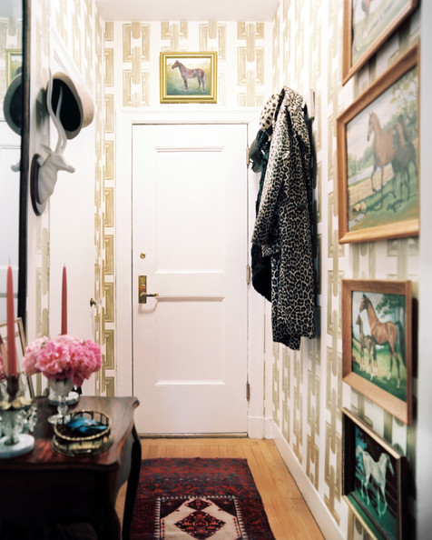 Entry framed horse portraits and chain link wallpaper in an entryway