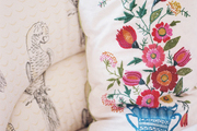 An embroidered pillow placed on an upholstered chair