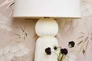 A detail of a white fringe table lamp.