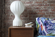 A midcentury bedside table and paper lamp stand in front of an exposed brick wall in the master bedroom.