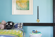 A white wicker elephant table and turquoise walls in a kids' bedroom
