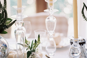 Glass candlesticks and white pumpkins decorating a table