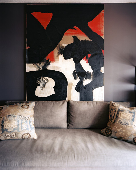 Wall Art - A painting hung above a gray couch with a pair of pillows