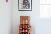 Stacked wooden chairs below a framed photograph