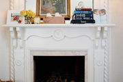 A white fireplace mantel with a pair of shaded sconces