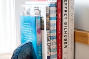 A detail of books with a gemstone bookend.