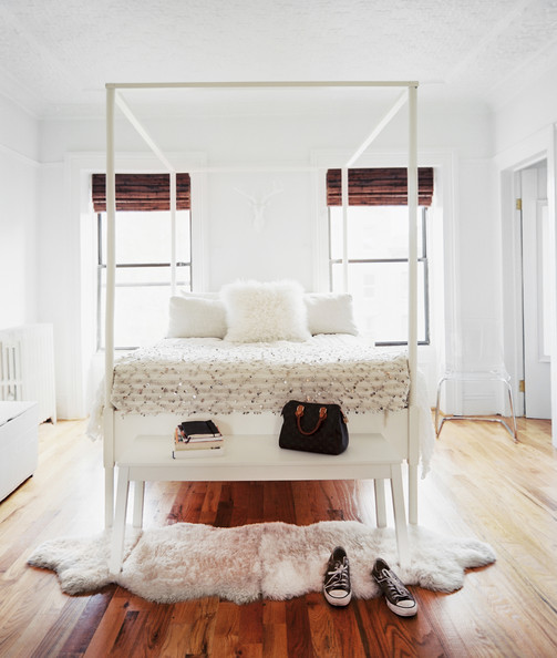 White Bedroom - A white bench and a pair of sheepskin rugs at the foot of a white canopy bed