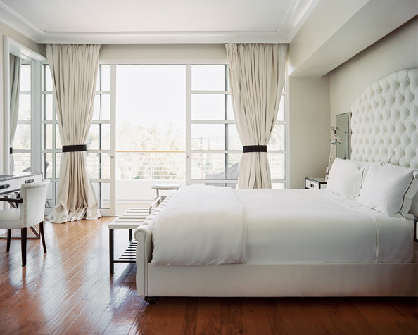 Windows - A guest room filled with white furniture and linens