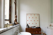 A bathroom with a marble-clad soaking tub, parquet floors, and contemporary art